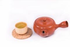 Heißer grüner Tee so köstlich und Teekanne auf weißem Hintergrund Lizenzfreie Stockfotografie