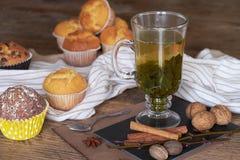 Heißer grüner Tee und frische Muffins auf einem Holztisch Stockbilder