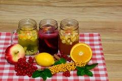 Heißer Herbst trinkt in den Weckgläsern in der Zusammensetzung Frucht, Beeren, Niederlassungen und Zweige des Viburnumwegdorns Stockbilder