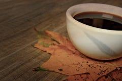 Heißer Herbstschwarz-Espressokaffee auf einem Holztisch und einem Herbst m Stockbild
