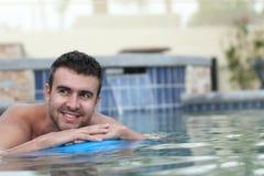Heißer junger Mann, der auf eine Matratze im Wasserpool schwimmt Lizenzfreie Stockfotografie