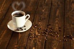 Heißer Kaffee auf einem Holztisch im Sonnenaufgang Lizenzfreies Stockbild
