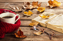 Heißer Kaffee, Buch, Gläser und Herbstlaub auf hölzernem Hintergrund