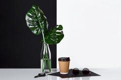 Heißer Kaffee in der braunen Papierschale und im Grün verlässt in der Glasflasche, die auf Tabelle mit Schwarzweiss-Wand auf Hint Lizenzfreie Stockbilder