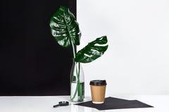 Heißer Kaffee in der braunen Papierschale und im Grün verlässt in der Glasflasche, die auf Tabelle mit Schwarzweiss-Wand auf Hint Stockfotos