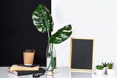 Heißer Kaffee in der braunen Papierschale und im Grün verlässt in der Glasflasche, die auf Tabelle mit Schwarzweiss-Wand auf Hint Lizenzfreies Stockbild
