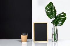 Heißer Kaffee in der braunen Papierschale und im Grün verlässt in der Glasflasche, die auf Tabelle mit Schwarzweiss-Wand auf Hint Stockbilder