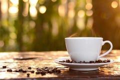 Heißer Kaffee in der Schale auf unscharfem dunkelgrünem Naturhintergrund Stockfotografie