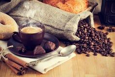 Heißer Kaffee der Schale mit Bohnen und Pralinen Stockbild