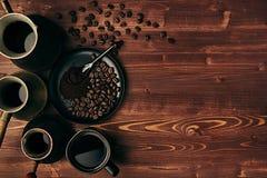 Heißer Kaffee in der schwarzen Schale und türkisches Töpfe cezve mit Bohnen, Untertasse mit Kopienraum auf braunem altem Hintergr Lizenzfreies Stockfoto