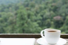 heißer Kaffee in der weißen Schale auf hölzerner Tabelle mit grünem Natur backgrou Stockbild