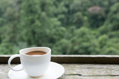 heißer Kaffee in der weißen Schale auf hölzerner Tabelle mit grünem Natur backgrou Lizenzfreies Stockbild