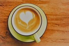 Heißer Kaffee des Cappuccinos mit Schaumherzform auf dem Holztischhintergrund Stockbilder