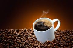 Heißer Kaffee in einem weißen Becher, der mit Kaffeebohne umgibt Lizenzfreies Stockfoto