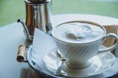 Heißer Kaffee in einer Schale auf Tabelle Abbildung der roten Lilie Stockfotos