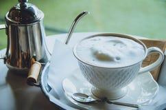 Heißer Kaffee in einer Schale auf Tabelle Abbildung der roten Lilie Stockbilder