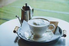 Heißer Kaffee in einer Schale auf Tabelle Abbildung der roten Lilie Stockbild
