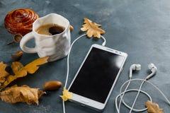 Heißer Kaffee im Becher mit Handy und Kopfhörern Stockfotografie