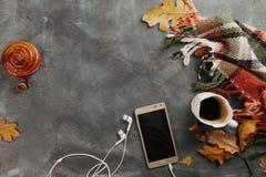 Heißer Kaffee im Becher und Brötchen, Handy mit Kopfhörern und autu Lizenzfreie Stockfotos