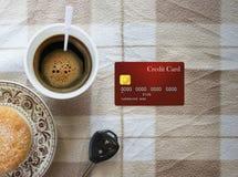Heißer Kaffee im Plastikschalen-, Bäckerei-, Kreditkarte- und Autoschlüssel auf ta Stockfoto