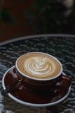 Heißer Kaffee Latte mit schöner Lattekunst auf keramischem Glas im lo Stockfoto
