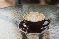 Heißer Kaffee Latte mit schöner Schaumkunst auf Glastisch outdoor Stockfotografie