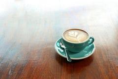 Heißer Kaffee mit Blattform Lattekunst auf der hölzernen Tabelle Stockfoto