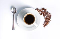 Heißer Kaffee mit Bohnen auf einem weißen Hintergrund Lizenzfreies Stockfoto