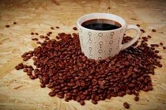 Heißer Kaffee mit Bohnen auf hölzerner Beschaffenheit Stockbild