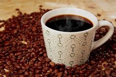 Heißer Kaffee mit Bohnen auf hölzerner Beschaffenheit Stockbilder