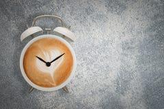 Heißer Kaffee mit schaumigem Schaum im weißen Weckerdesign ist Kaffee Stockfotografie