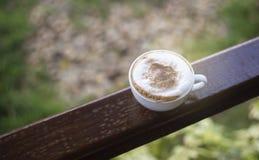 Heißer Kaffee morgens auf hölzerner Bar mit unscharfem Garten im Hintergrund, selektiver Fokus, gefiltertes Bild, Lichteffekt add Lizenzfreie Stockfotografie