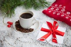 heißer Kaffee, roter warmer Pullover und Geschenk mit einem roten Bogen auf einem schneebedeckten Hintergrund Lizenzfreie Stockfotos