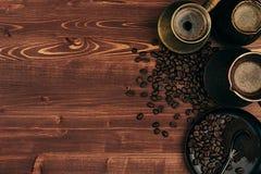 Heißer Kaffee in schäbigem türkischem Töpfe cezve mit Bohnen, Untertasse mit Kopienraum auf braunem altem Hintergrund des hölzern Lizenzfreies Stockfoto