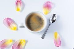 Heißer Kaffee umgeben durch Tulpenblumenblätter stockfoto