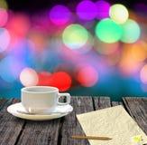 Heißer Kaffee und Briefpapier auf Tabelle mit bokeh stockbild