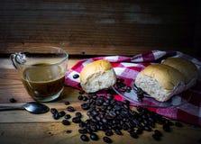 Heißer Kaffee und Brot auf einem Holztisch Stockfoto