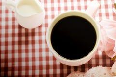 Heißer Kaffee und frische Milch- und süßerosa Rosen auf dem Tisch Stockfoto