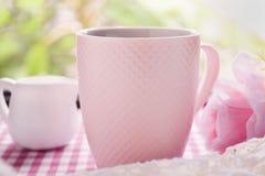 Heißer Kaffee und frische Milch- und süßerosa Rosen auf dem Tisch Stockfotografie