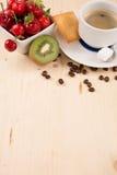 Heißer Kaffee und geschmackvoller Kuchen und Früchte auf dem Holztisch Lizenzfreie Stockbilder