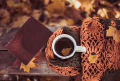 Heißer Kaffee und rotes Buch mit Herbstlaub auf dem hölzernen Saison Hintergrund - entspannen Sie sich Konzept Lizenzfreie Stockfotos