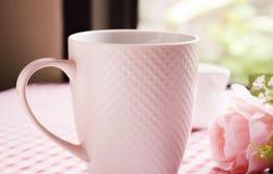 Heißer Kaffee und süße rosa Rosen auf dem Tisch Stockfotografie