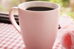 Heißer Kaffee und süße rosa Rosen auf dem Tisch Lizenzfreies Stockbild