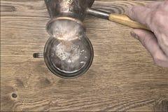 Heißer Kaffee wird aus einem Topf des türkischen Kaffees in eine Schale gegossen, Hände sind sichtbar Lizenzfreie Stockfotos