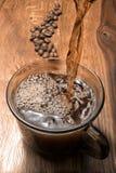 Heißer Kaffee wird aus einem Topf des türkischen Kaffees in eine Schale gegossen, Hände sind sichtbar Stockbild