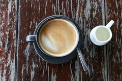 Heißer Lattekaffee in der schwarzen Schale auf hölzerner Tischplatteansicht Stockfotos
