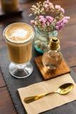 Heißer Lattekaffee im transparenten Glas auf hölzerner Tabelle Stockfotos