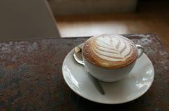 Heißer Lattekaffee mit Blattform in der weißen Schale auf der rostigen Tabelle Stockfoto