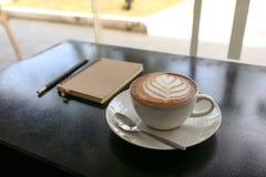 Heißer Lattekaffee mit Blattform in der weißen Schale, im Notizbuch und im Bleistift Lizenzfreie Stockfotos