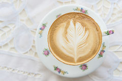 Heißer Lattekunstkaffee in der Weinlese höhlen auf dem Tisch Stockfoto
